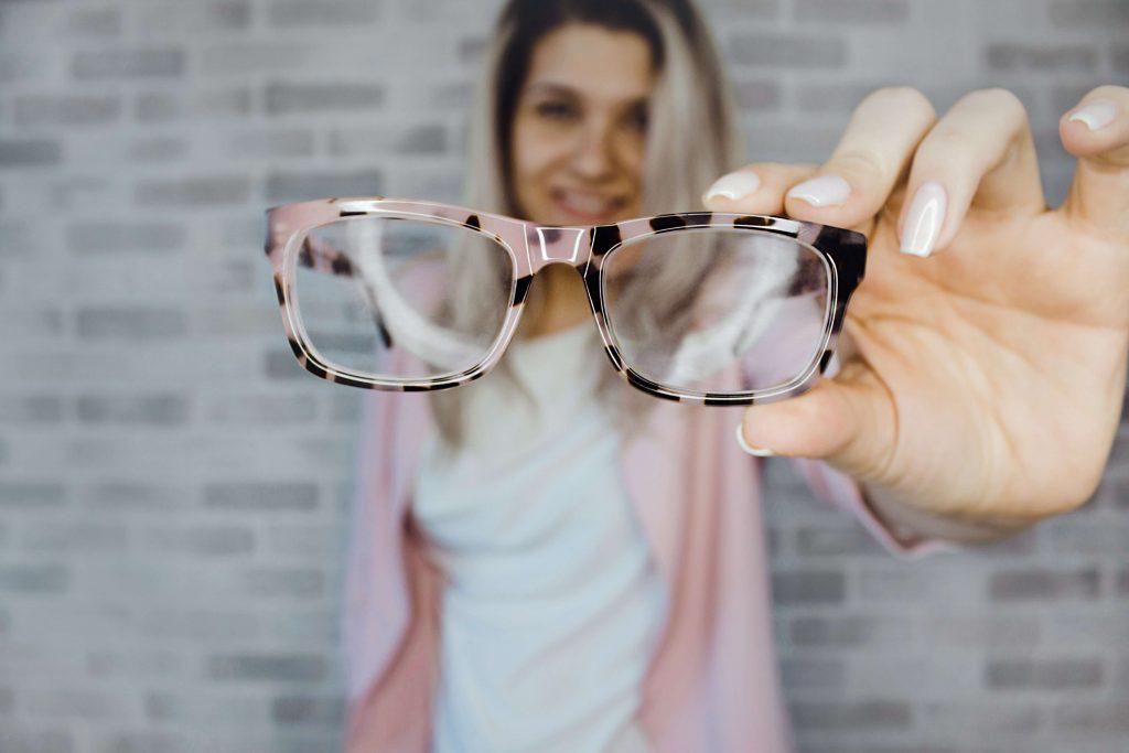 Frau hält eine Brille vor sich