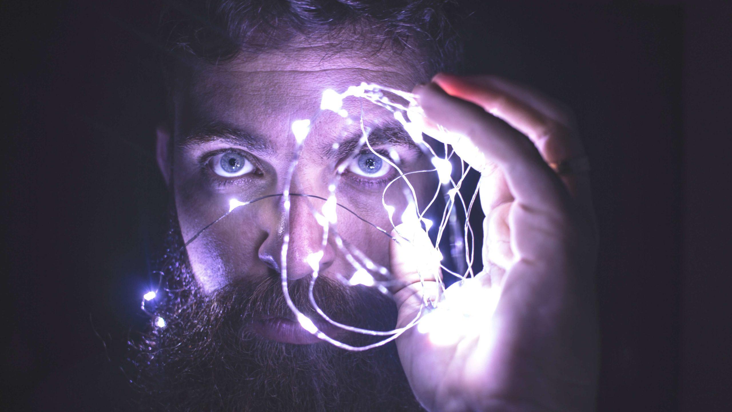 Mann hält Lichterkette vors Gesicht