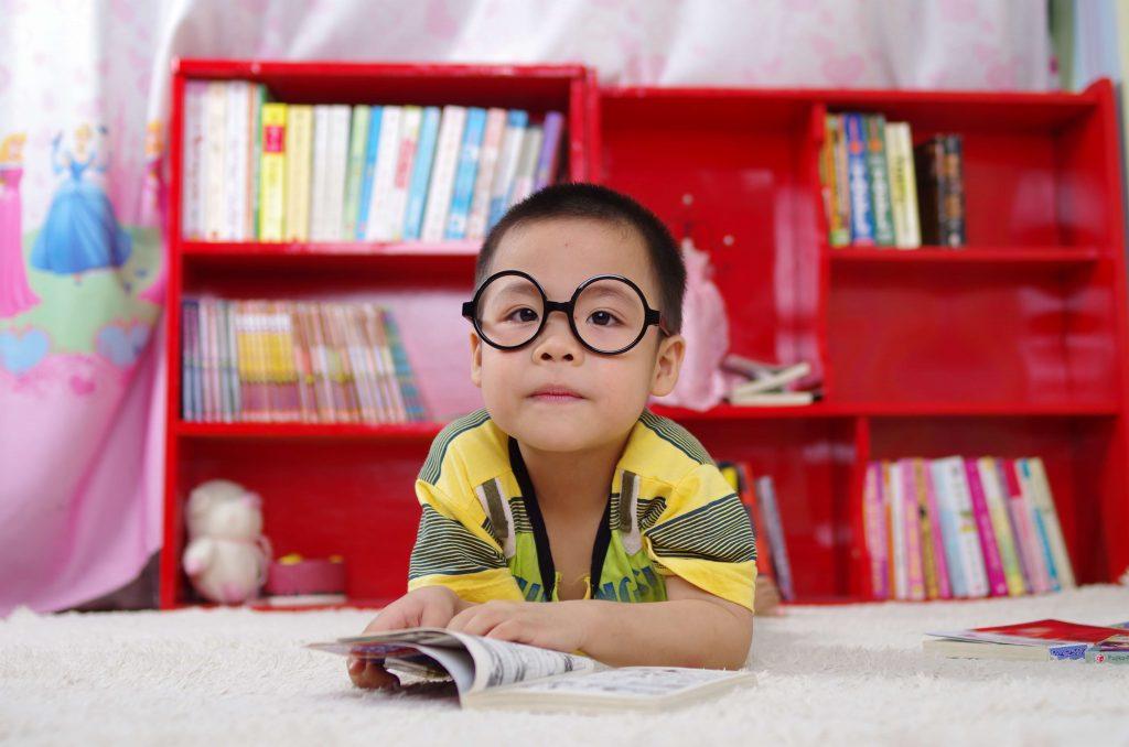 Kurzsichtigkeit bei Kindern - Junge mit Brille vor rotem Regal