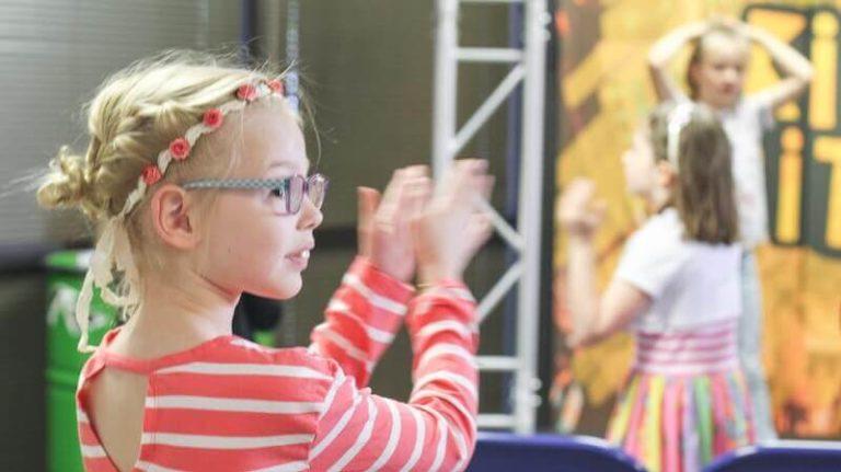Kurzsichtigkeit bei Kindern - Mädchen mit Brille applaudiert