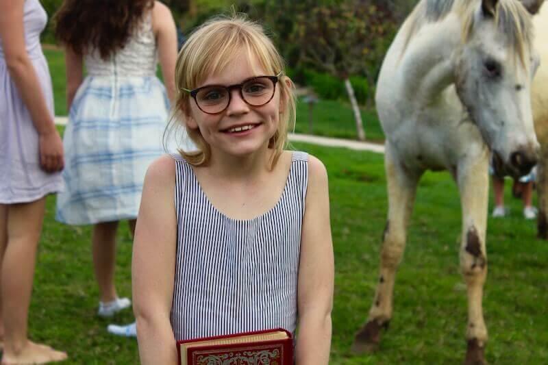 Kurzsichtigkeit bei Kindern - Mädchen mit Brille vor einem Pferd