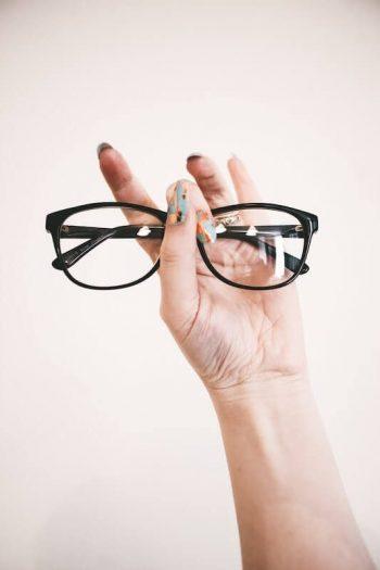 Frauenhand hält Brille hoch