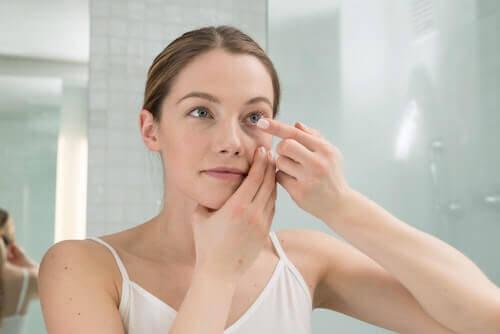 Frau nimmt Kontaktlinse aus dem Auge