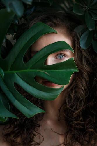 Frau steht hinter einem großen grünen Blatt, das ihr Gesicht verdeckt