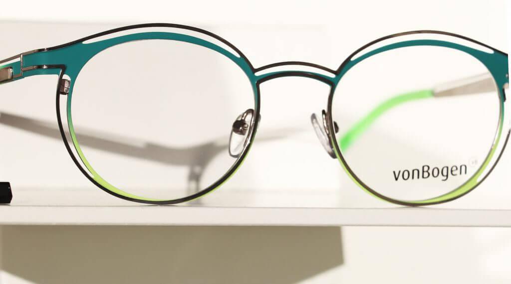 Doppelsteg Brille mit runden Gläsern. Gestell in dunkelgrün mit neongrünen Akzenten