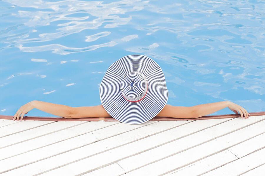 Frau mit Sonnenhut am Pool